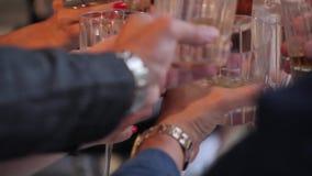 戴威士忌酒杯酒精和眼镜的人们庆祝在桌上 人叮当声玻璃用香槟和 影视素材