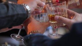 戴威士忌酒杯酒精和眼镜的人们庆祝在桌上 人的手戴威士忌酒眼镜的  股票视频