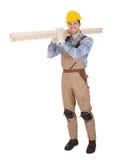 戴安全帽和运载木材的工作者 免版税库存图片