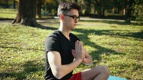 戴实践凝思Sukhasana坐的姿势用被折叠的手的眼镜的年轻人 人的人坐地毯 股票录像