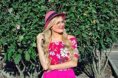 戴帽子和眼镜的美丽的白肤金发的女孩 在露天 在她的绿色叶子后 照亮由太阳 免版税图库摄影