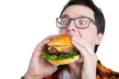 戴拿着一个新鲜的汉堡的眼镜的一个年轻人 一名非常饥饿的学生吃便当 热的有用的食物 暴食的概念 图库摄影