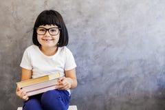 戴拿着书的眼镜的黑发小女孩由墙壁 图库摄影