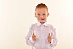 戴摆在制服的眼镜的一个白种人基本的年龄男孩隔绝在白色背景 学校和教育概念 免版税库存图片