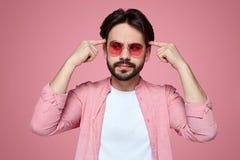 戴时髦的成套装备和太阳镜的帅哥看与周道的表示,保留在他的头的食指 库存图片