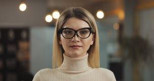 戴时髦的眼镜的年轻成功的女实业家画象看在办公室工作区的照相机身分 影视素材