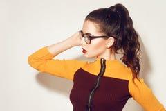 戴时髦的眼镜的秀丽时尚深色的式样女孩 有完善的构成,时髦橙色和红色礼服的性感的妇女 库存照片
