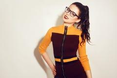 戴时髦的眼镜的秀丽时尚深色的式样女孩 有完善的构成,时髦橙色和红色礼服的性感的妇女 免版税库存照片