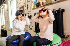 戴明亮的滑稽的太阳镜的美丽的时髦的姐妹 免版税图库摄影