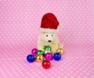 戴有圣诞节球的北极熊玩偶一个圣诞老人帽子 免版税库存照片