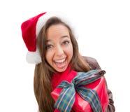 戴有弓被包裹的礼物的Iisolat的激动的青少年的女孩圣诞节圣诞老人帽子 库存照片