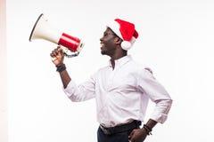 戴有扩音器的年轻非裔美国人的人一个圣诞老人帽子隔绝在白色背景 库存照片