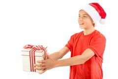 戴有礼物的年轻十几岁的男孩一个圣诞老人圣诞节帽子 库存图片