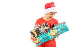 戴有礼物的年轻十几岁的男孩一个圣诞老人圣诞节帽子 免版税库存图片