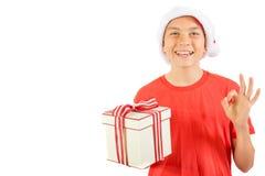 戴有礼物的年轻十几岁的男孩一个圣诞老人圣诞节帽子 库存照片