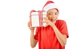 戴有礼物的年轻十几岁的男孩一个圣诞老人圣诞节帽子 免版税图库摄影
