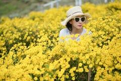 戴有黄色花的妇女一个帽子 库存照片