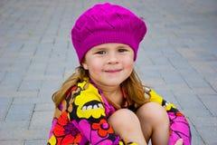 戴桃红色编织帽子的女孩 免版税库存照片