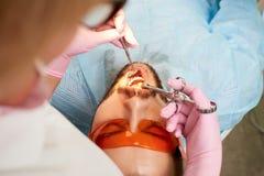 戴橙色眼镜的年轻男性客户安排牙射入进行由牙医在桃红色手套 免版税库存图片