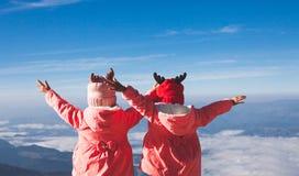 戴毛线衣和温暖的帽子的两个亚裔儿童女孩举他们的看美丽的薄雾和山与的胳膊 库存图片