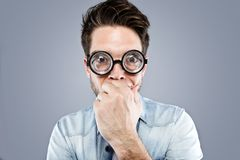 戴滑稽的眼镜的英俊的年轻人耍笑和做在灰色背景的滑稽的面孔 库存图片