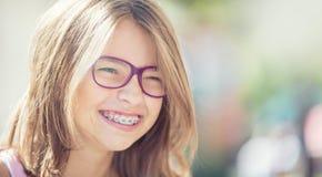 戴牙齿括号和眼镜的愉快的微笑的女孩 年轻逗人喜爱的加州 免版税库存图片