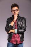 戴皮夹克和眼镜的沉思年轻人 库存图片