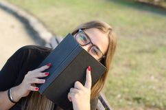 戴看对您和拿着书的眼镜的疯狂的白肤金发的女孩 图库摄影