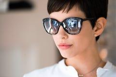 戴眼镜买太阳镜的眼镜师的年轻美丽的妇女 库存图片