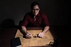 戴眼镜的一个人通过放大镜审查世界的地图 免版税库存图片