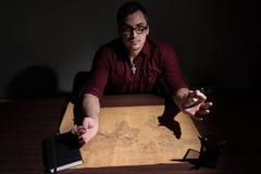戴眼镜的一个人通过放大镜审查世界的地图 库存图片