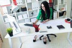 戴眼镜的一个女孩在办公室坐在桌上并且拿着一个电话、一支铅笔和键入的文本在键盘 免版税库存照片