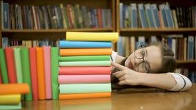 戴眼镜的一个女孩计数多少本书 影视素材