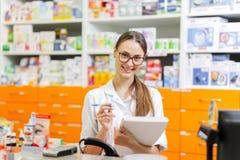 戴眼镜的一个年轻的宜人的深色头发的女孩,穿戴在医疗总体,在笔记本写笔记在现金 库存照片
