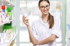 戴眼镜的一个年轻的稀薄的棕色毛发的夫人,穿戴在实验室外套,拿着在她的右手的一个小瓶子在新 库存照片