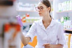 戴眼镜的一个年轻稀薄的棕色毛发的女孩,穿戴在实验室外套,蹲下,审查在架子的医学在a 免版税库存图片