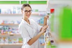 戴眼镜的一个微笑的亭亭玉立的深色头发的夫人,穿一件白色外套,立场在现代药房的架子旁边 库存照片