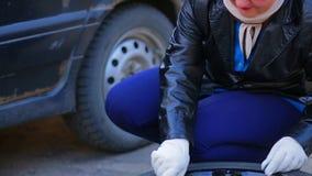 戴眼镜的一名妇女松开在车胎的插座在盘上 影视素材