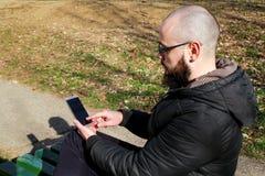 戴眼镜的人是坐和使用巧妙的电话 免版税库存图片