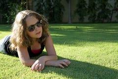 戴眼镜的俏丽的女孩在草 免版税库存照片