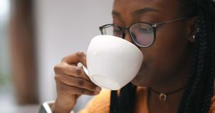 戴眼镜的喝咖啡热奶咖啡的美丽的非洲女孩画象  影视素材