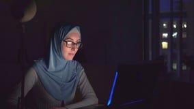 戴眼镜的回教女孩和与笔记本的一hijab在黑暗 股票录像