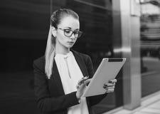 戴眼镜的女商人使用片剂,黑白 免版税库存照片