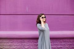 戴眼镜的女孩在紫色墙壁上 免版税库存图片