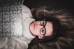 戴眼镜的女孩读您喜爱的小说的 免版税库存图片