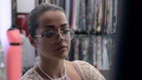 戴眼镜的女孩选择纺织品fabri 股票视频
