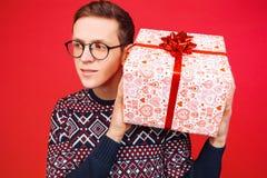 戴眼镜的好奇人,拿着礼物盒的一个人,震动它发现什么是在箱子里面,在红色背景 库存图片