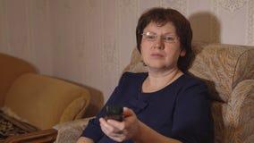 戴眼镜的妇女交换有遥控的电视频道 免版税库存照片