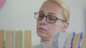 戴眼镜的妇女在图书馆在书架的书中搜寻 影视素材
