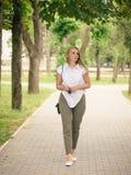 戴眼镜的妇女在手上走在公园的查寻 免版税图库摄影